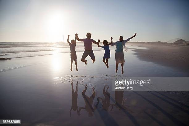 Family jumping together on a beach
