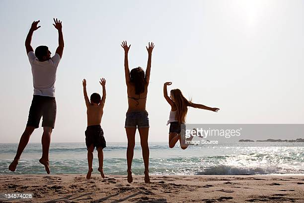 Family jumping up in the air on a beach