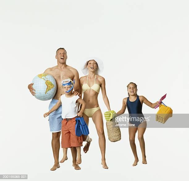 Family jumping, wearing beach wear, portrait