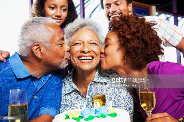 Family kissing African American woman on birthday