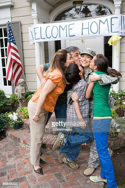 Family kissing soldier