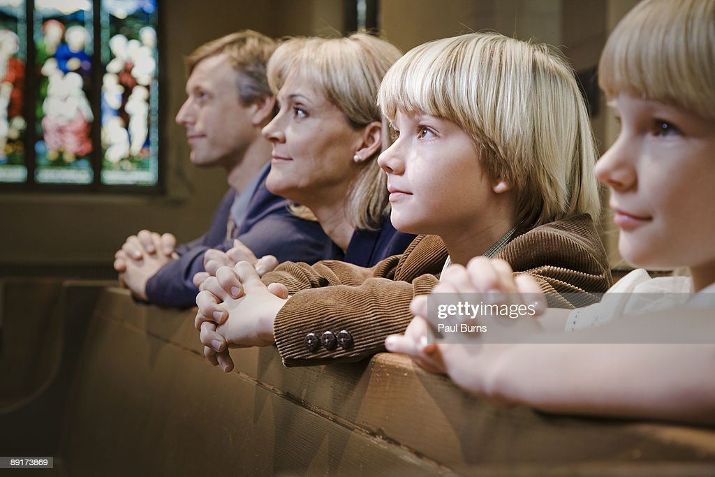 Family Kneeling and Praying in Church : Stock Photo