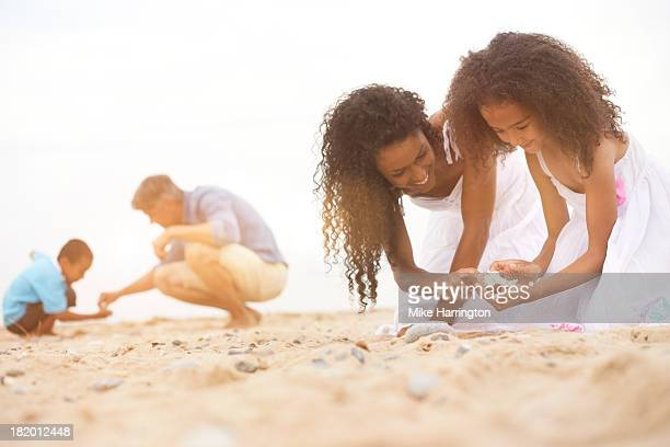 Family kneeling on beach searching for shells.
