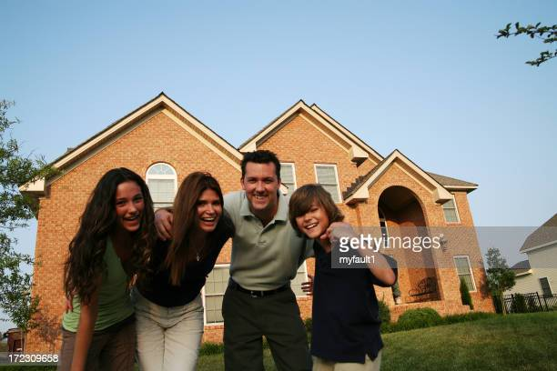 Family laughing in fromt of their home