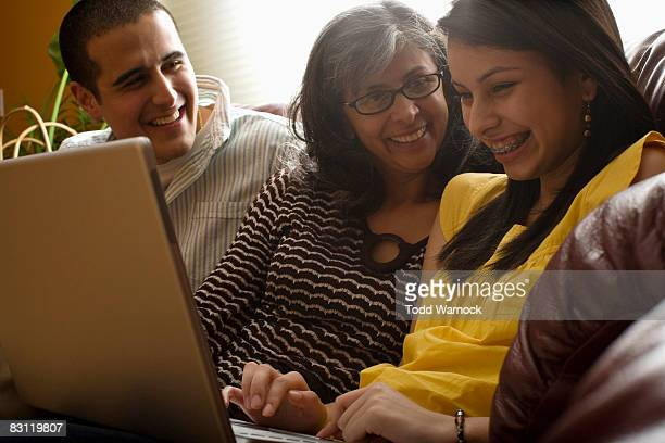 family laughing using laptop