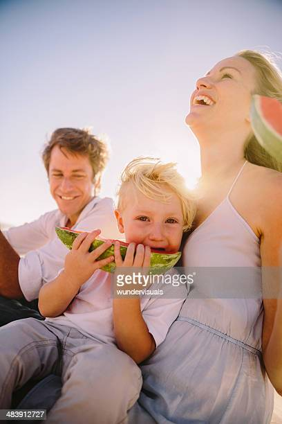 Family laughing while eating watermelon