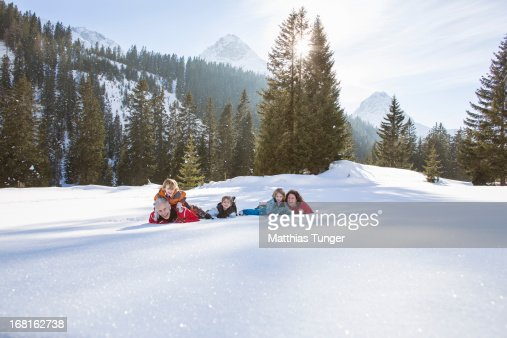 Family laying around in the snow : Foto stock