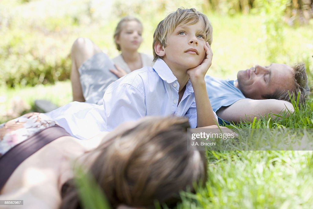 Family laying in grass : Stock Photo