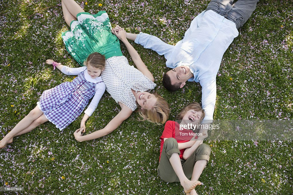 Family laying in grass together : Stock Photo