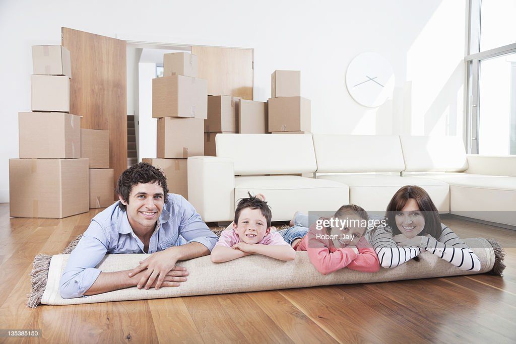 Family laying on carpet in new home : Stock Photo