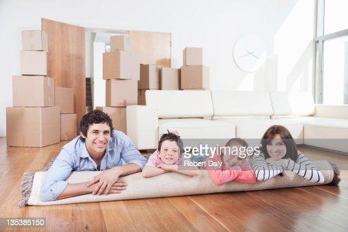Familia que descansan en alfombra en Nuevo hogar : Foto de stock