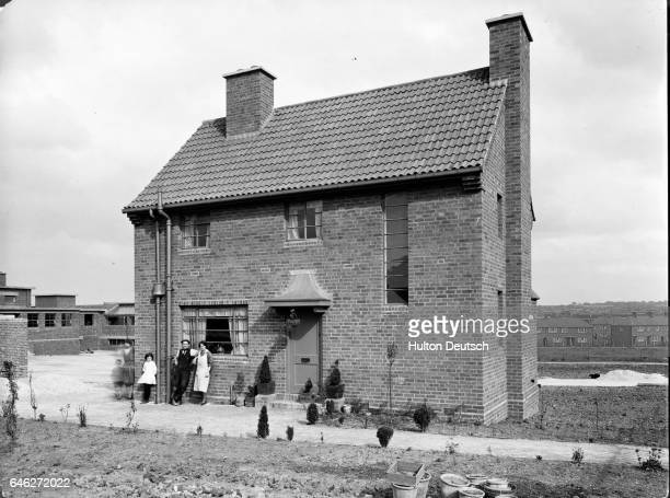 A family lean proudly against the wall of their newly built detached home where the garden is still in the early stages of development UK ca 1948