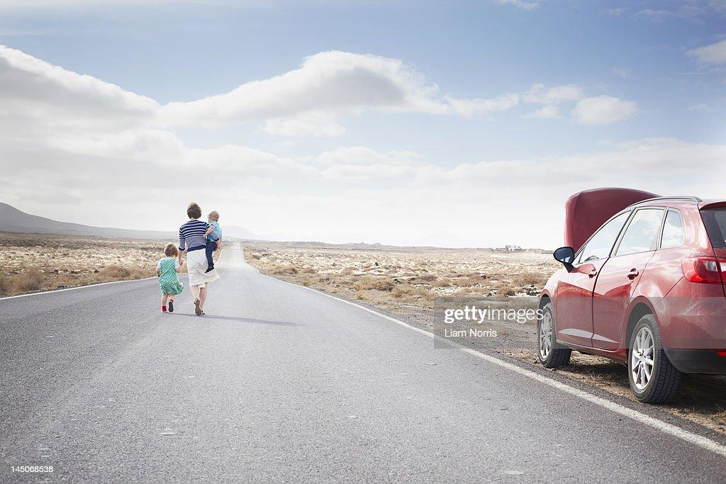 Family leaving broken down car on road