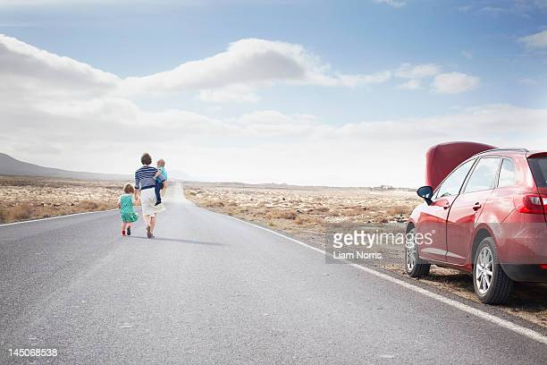 Family leaving broken down car on road