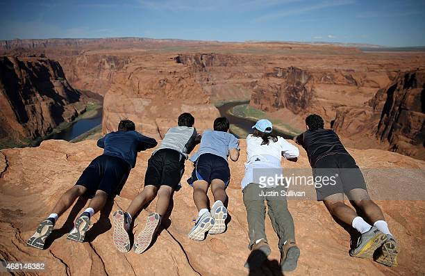 A family lies on the edge of a cliff to view the Colorado River at Horseshoe Bend on March 30 2015 in Page Arizona As severe drought grips parts of...