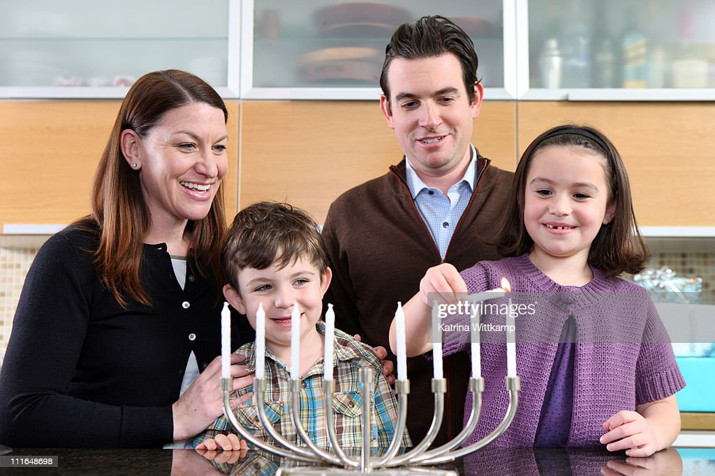 Family lighting the menorah.