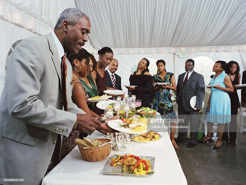 Family lining up to fill plates at buffet table at celebration : Stockfoto