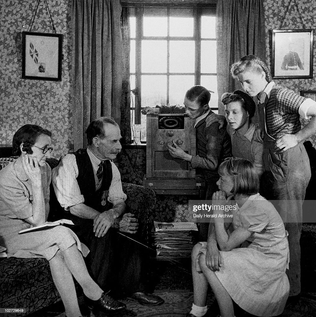 Family listening to a speech by Winston Churchill, 19 May 1945. Mr and Mrs Cooper and family tuning in their wireless to listen to a speech by Prime Minister Winston Churchill. 'Mr and Mrs Cooper have two sons in the Army, one on the land, two ATS daughters, one WAAF, two landgirls and a girl at school. Those left at home listen to Churchill.' Photograph by James Jarche.