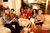 Family listening to man play guitar