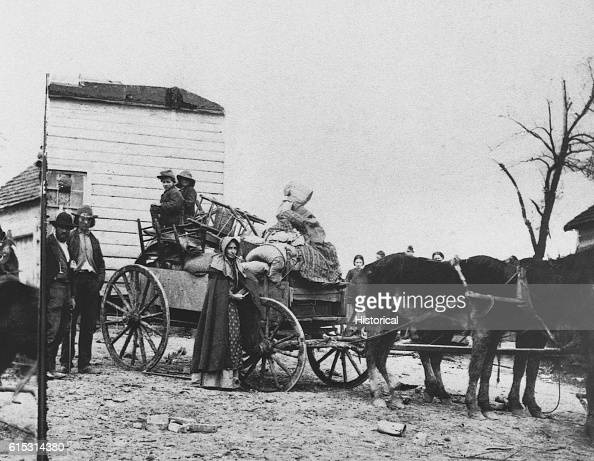 A family living in the northern United States loads their horsedrawn wagon as they prepare to flee from advancing Confederate troops during the Civil...