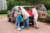 Family loading car for trip