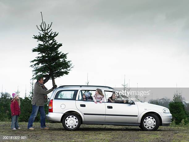 Family loading Christmas tree onto roof of car