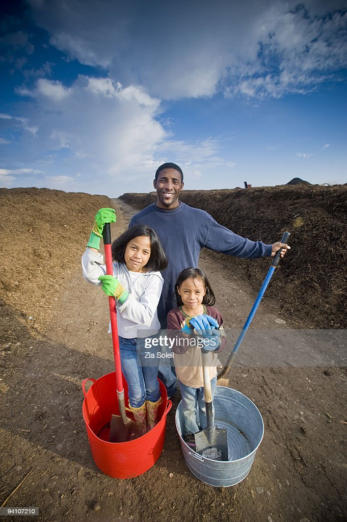 family loading free mulch from municipal landfill : Stock Photo