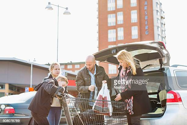 Family loading groceries in car trunk at parking lot