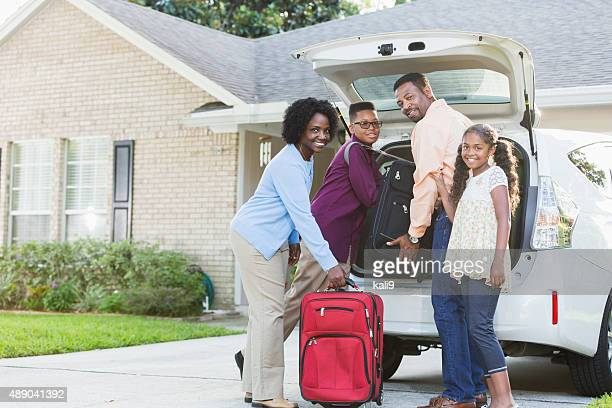 Family loading luggage into car going on vacation