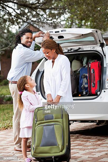 Family loading luggage into car