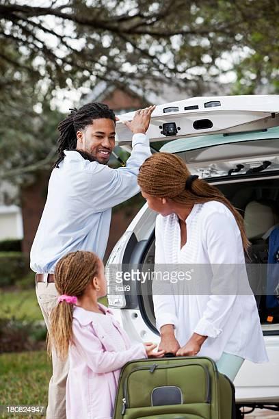 Family loading luggage into car