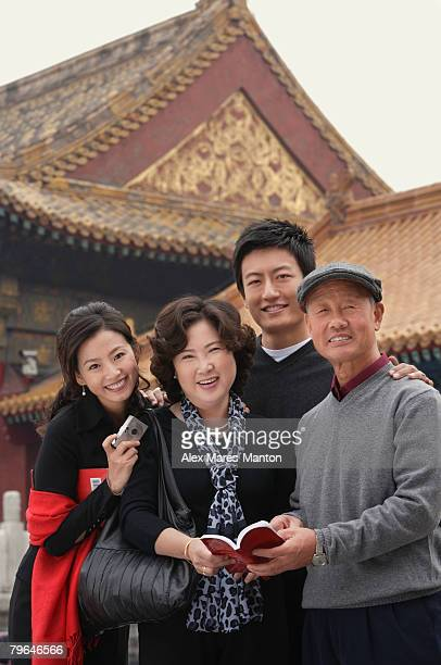 A family look at the camera as they pose in front of The Forbidden City, Beijing