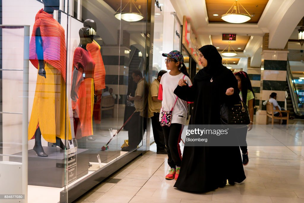 A family look at the window display of a fashion store while shopping at the Souq Sharq mall in Kuwait City, Kuwait, on Monday, Aug. 14, 2017. Kuwait will issue a tender to build the estimated $1.2 billion Dibdibah solar-power plant in the first quarter of 2018 as part of the countrys plans to produce 15 percent of power from renewable energy by 2030. Photographer: Tasneem Alsultan/Bloomberg via Getty Images