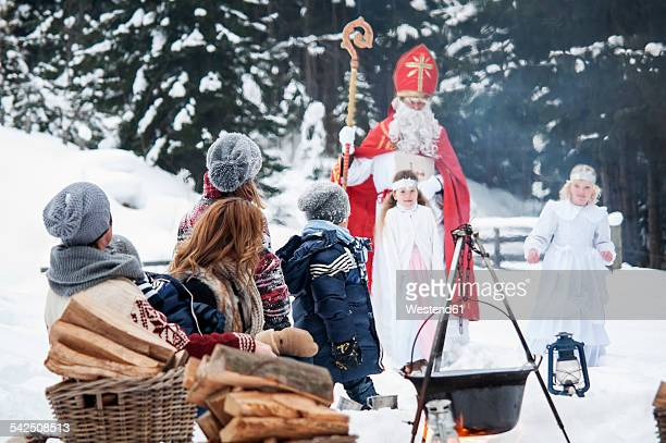Family looking at angels and Santa Claus in snow