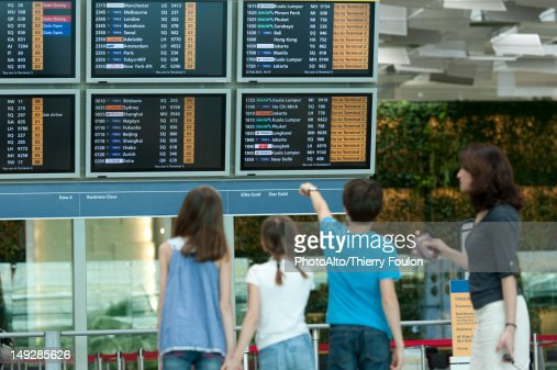 Family looking at arrival departure board, rear view