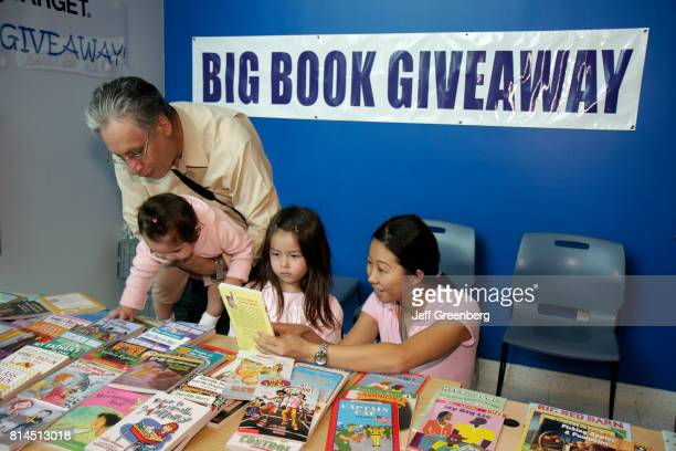 A family looking at books at the Children's BookFest at Hollywood Branch Library