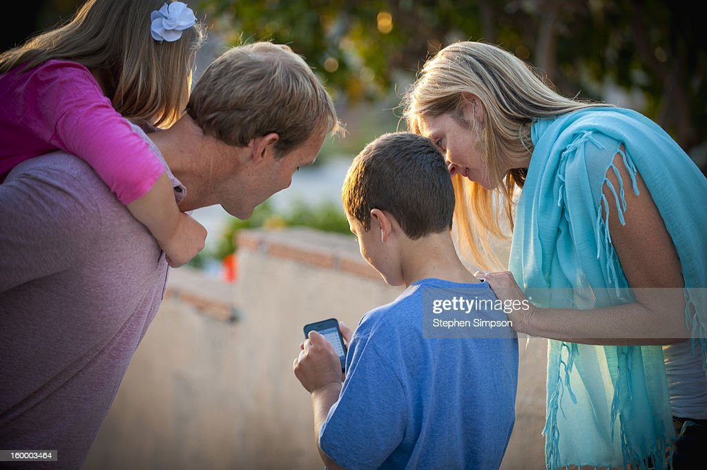 family looking at cell phone screen : Stock Photo