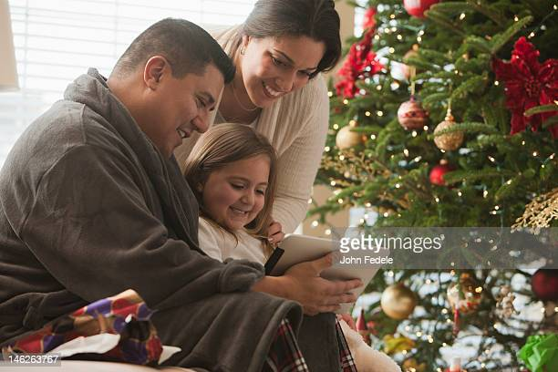 Family looking at digital tablet on Christmas morning