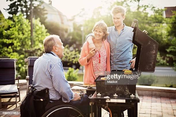 Family looking at disabled man barbecuing at yard