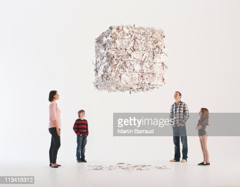 Family looking at floating paper bale : Foto de stock
