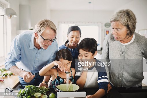 Family looking at girl preparing food at kitchen counter