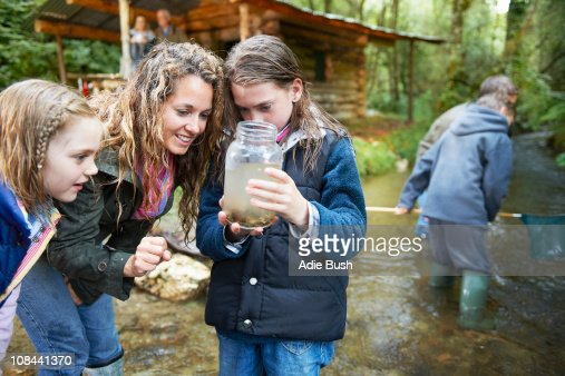 Family looking at insects in jam jar