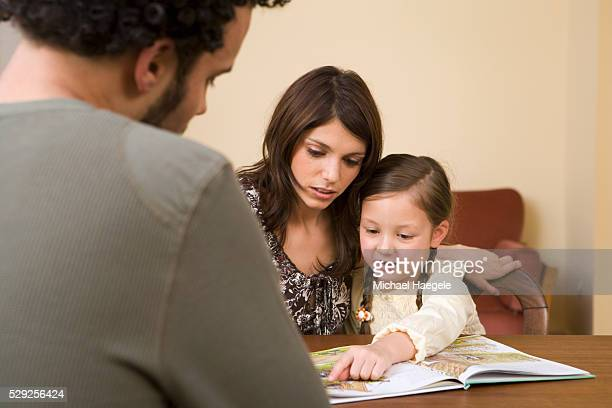 Family Looking at Picture Book