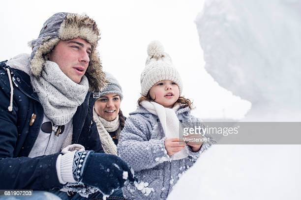 Family looking at snowman