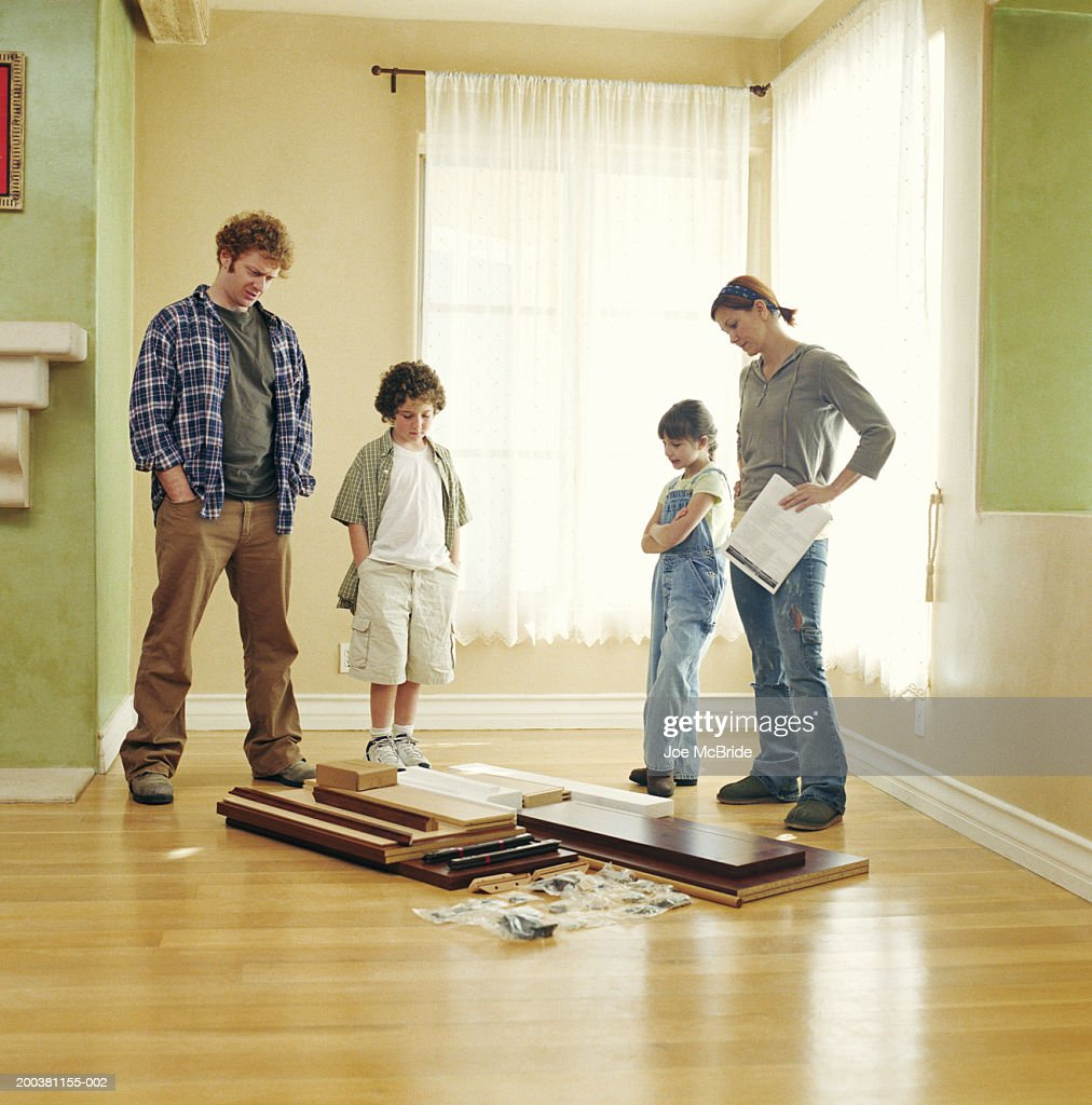 Family looking at unassembled furniture on floor : Stock Photo