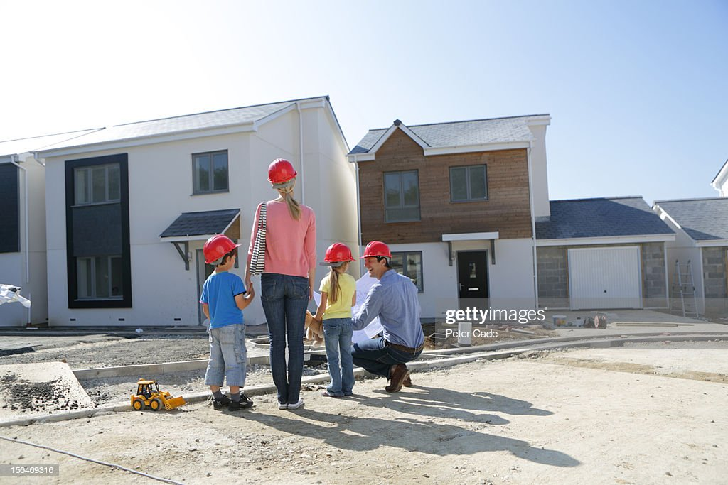 Family looking at unfinished new build house : Stock Photo