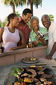 Family Looking at Video Camera During Barbecue