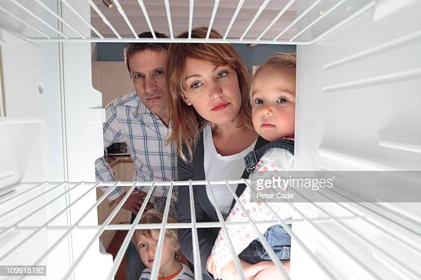 family looking into empty fridge