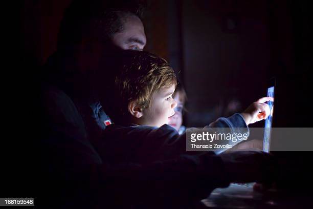 Family looking to a tablet in the dark