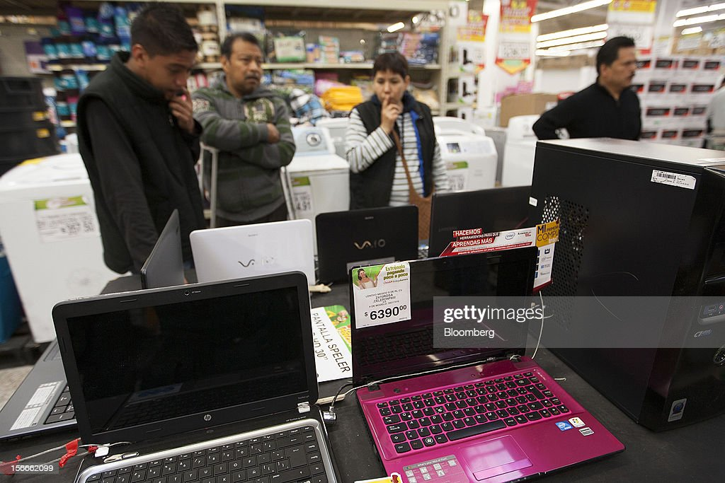 A family looks at laptop computers inside a Wal-Mart de Mexico SAB de CV's Bodega Aurrera store in Mexico City, Mexico on Saturday, Nov. 17, 2012. El Buen Fin, Mexico's equivalent of Black Friday, when the year's biggest discounts are offered by participating stores, is held on the third weekend of November and will run through Nov. 19. Photographer: Susana Gonzalez/Bloomberg via Getty Images
